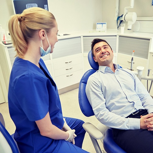 man sitting in dental chair and smiling at dentist in Idaho Falls