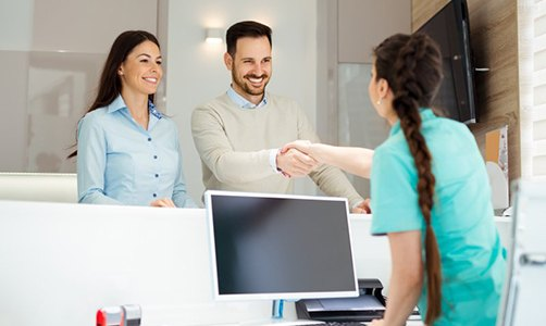 woman shaking hands with man over front desk