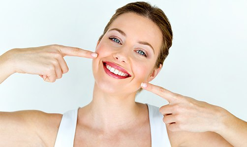 Woman pointing to teeth after smile makeover