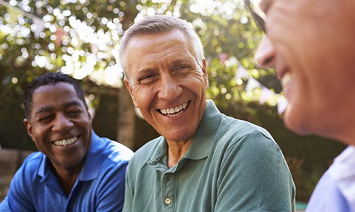 Three older men smiling after dental implant tooth replacement