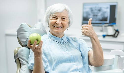 Older woman with dentures smiling and holding an apple