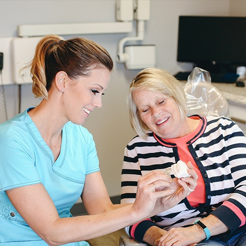 Dental team member showing patient a smile model during periodontal therapy appointment