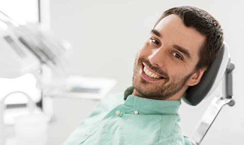 Man in dental chair smiling after root canal therapy