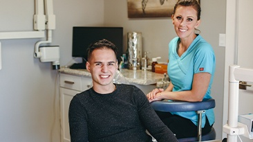 Young man and dental team member smiling after orthodontic treatment visit