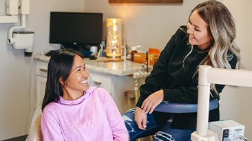 Dental team member smiling with relaxed patient thanks to sedation dentistry